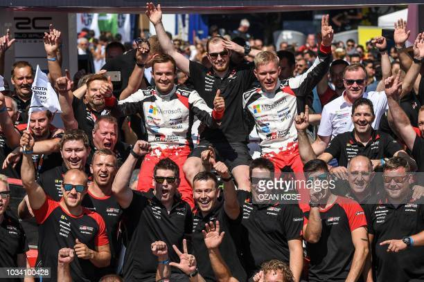 TOPSHOT Estonian driver Ott Tanak and his codriver Martin Jarveoja celebrate their victory with their Toyota team members at the end of the fourth...