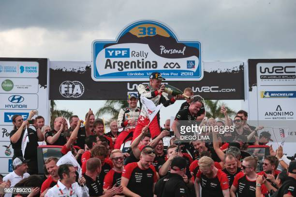 Estonian driver Ott Tanak sprays champagne as he celebrates with teammates on the final podium of the Argentina World Rally Championship in Villa...