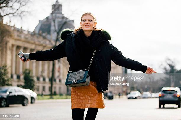 Estonian model Alexandra Elizabeth Ljadov has fun and wears eye makeup by Tom Pecheux a dark Kenzo puffer jacket a green fur lining Chanel purse and...