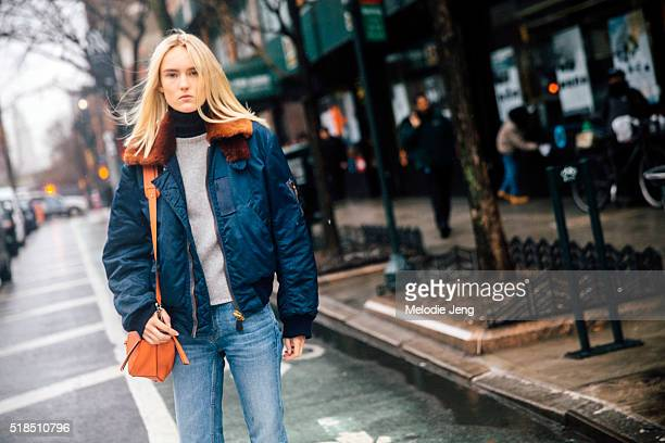 Estonian model Harleth Kuusik wears a blue bomber MA1 jacket with an orange fur collar a gray top light washed jeans and an orange Loewe puzzle bag...
