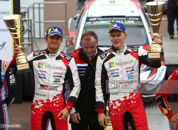 Estonian pilot Ott Tanak and co pilot Martin Jarveoja hold their winner's trophies as they celebrate winning the Wales Rally GB the 12th round of the...
