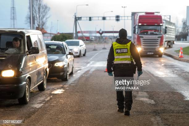 Estonian police controls drivers at the Ikla crossing point between Estonia and Latvia on March 14, 2020 as the government has declared a state of...