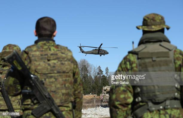 Estonian soldiers watch a US Army Blackhawk helicopter fly past following a joint military combat exercise on March 23 2017 near Tapa Estonia US...