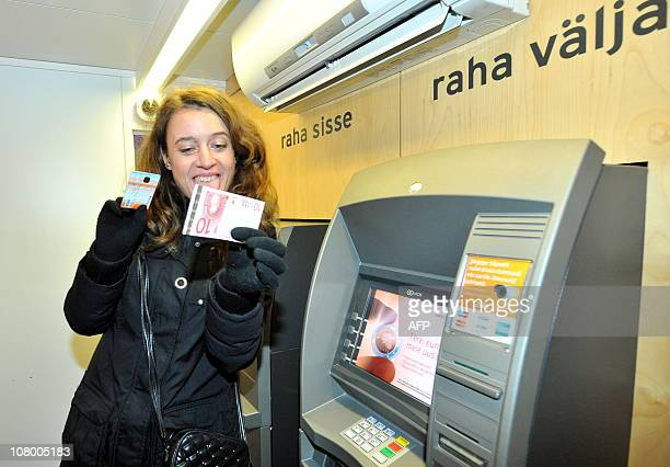 A Estonian woman receives her first euro note from the ATM on January 1 2011 in Tallinn Estonia Estonia adopted the European single currency at...