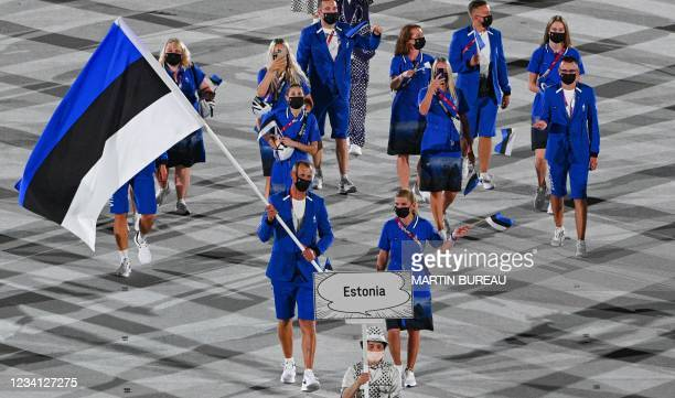 Estonia's flag bearer Tonu Endrekson and Estonia's flag bearer Dina Ellermann and their delegation parade during the opening ceremony of the Tokyo...