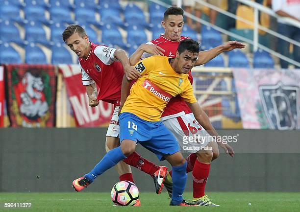 Estoril's forward Alisson Farias from Brazil tackled by SC Braga's Portuguese forward Pedro Santos and SC Braga's Brazilian midfielder Mauro during...