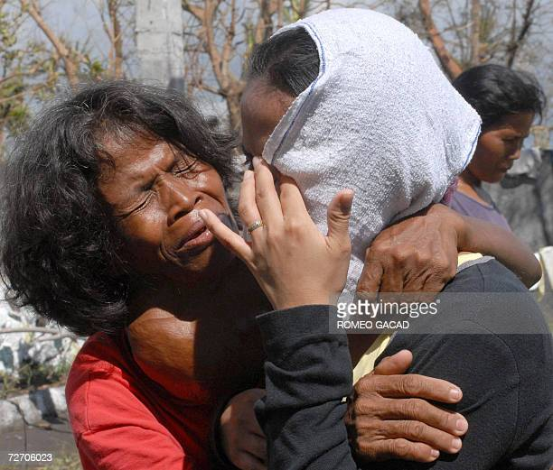 Estrella Balectar afflicted with goiter and Michelle Tolosa grieve for their missing relatives at an evacuation center in Padang village 03 December...