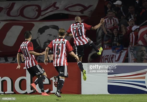 Estudiantes de La Plata's forward Diego Vera celebrates next to teammates midfielder Gaston Gil Romero and midfielder Joaquin Correa after scoring...