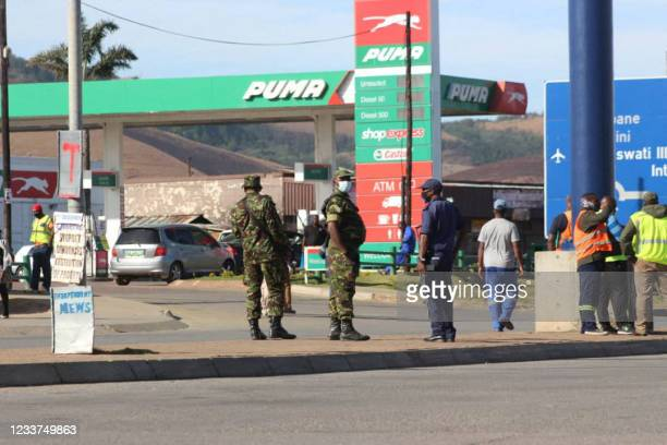 Eswatini soldiers and police officers are seen on the streets near the Oshoek Border Post between Eswatini and South Africa on July 1, 2021. -...