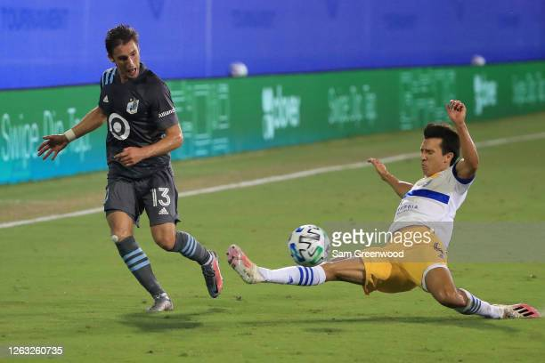 Ethan Finlay of Minnesota United fights for the ball with Danny Hoesen of San Jose Earthquakes during a quarter final match of MLS Is Back Tournament...