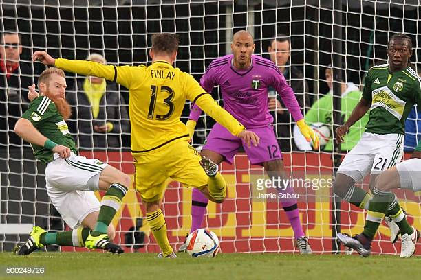 Ethan Finlay of the Columbus Crew SC moves in to shoot on goalkeeper Adam Kwarasey of the Portland Timbers as Nat Borchers of the Portland Timbers...