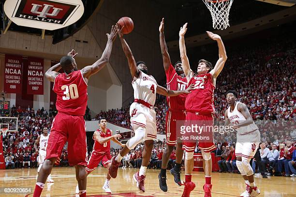 Ethan Happ Nigel Hayes and Vitto Brown of the Wisconsin Badgers defend against Robert Johnson of the Indiana Hoosiers in the first half of the game...