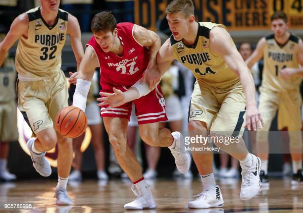 Ethan Happ of the Wisconsin Badgers and Isaac Haas of the Purdue Boilermakers battle for loose ball during the game at Mackey Arena on January 16...