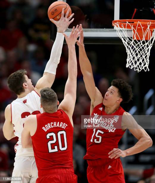 Ethan Happ of the Wisconsin Badgers attempts a shot while being guarded by Tanner Borchardt and Isaiah Roby of the Nebraska Huskers in the second...