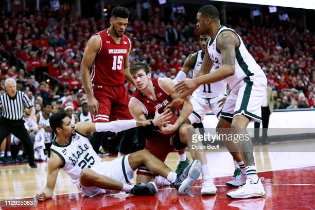 Ethan Happ of the Wisconsin Badgers calls for a timeout in the first half against the Michigan State Spartans at the Kohl Center on February 12 2019...