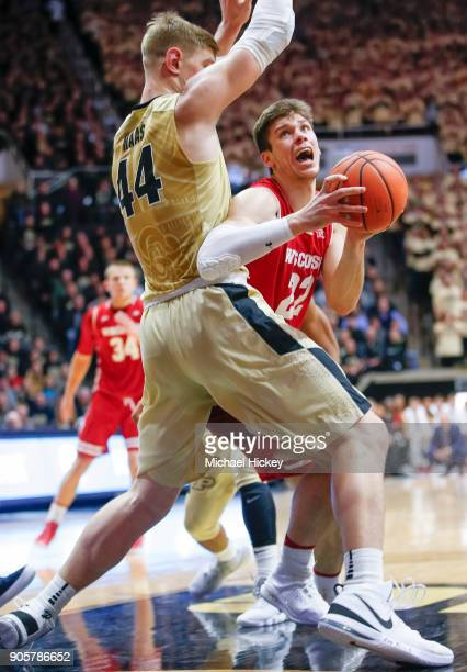 Ethan Happ of the Wisconsin Badgers looks to shoot as Isaac Haas of the Purdue Boilermakers defends at Mackey Arena on January 16 2018 in West...