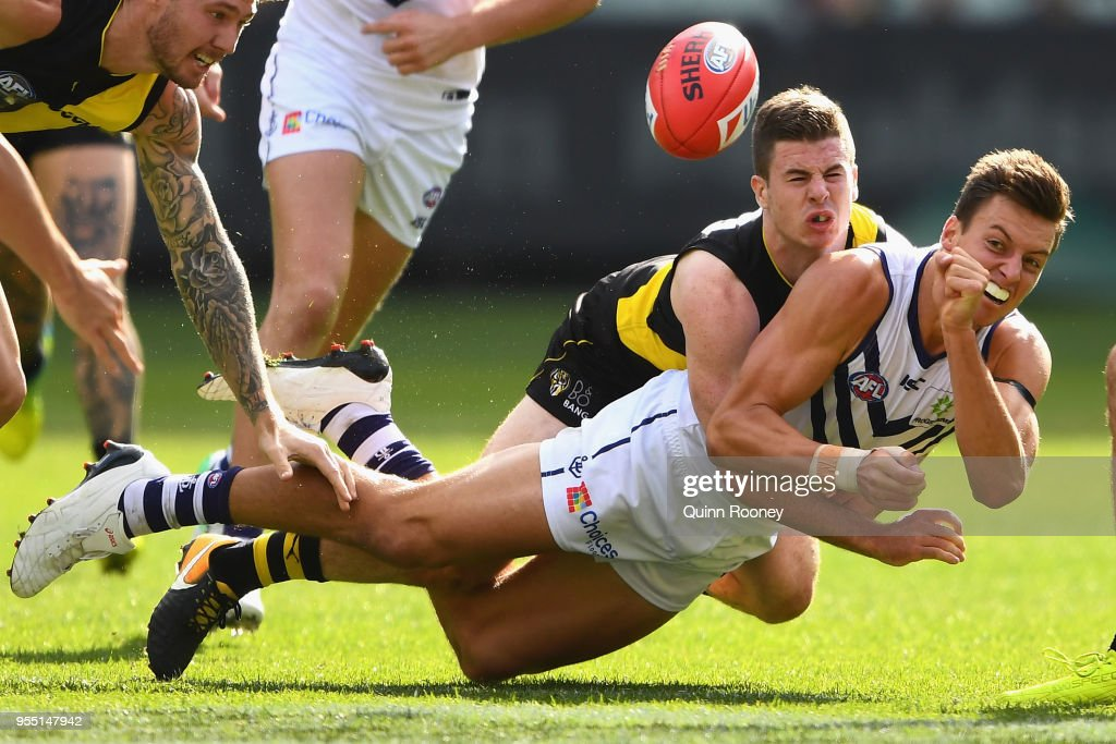 Ethan Hughes of the Dockers handballs whilst being tackled by Jack Higgins of the Tigers during the round seven AFL match between the Richmond Tigers and the Fremantle Dockers at Melbourne Cricket Ground on May 6, 2018 in Melbourne, Australia.