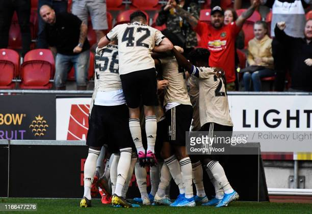 Ethan Laird of Manchester United U21 celebrates with his team mates after scoring his teams first goal of the match during the EFL Trophy match...