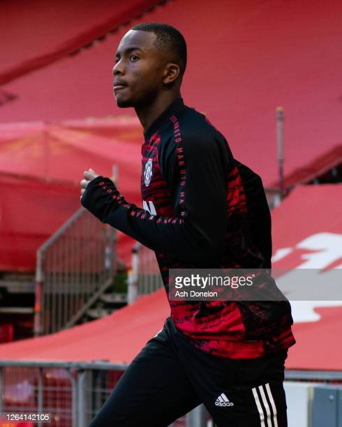 Ethan Laird of Manchester United warms up ahead of the UEFA Europa League round of 16 second leg match between Manchester United and LASK at Old...