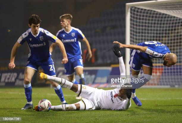 Ethan Laird of Milton Keynes Dons is challenged by Thomas O'Connor and Jordan Graham of Gillingham FC during the Sky Bet League One match between...