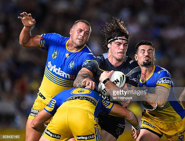 Ethan Lowe of the Cowboys is tackled by Danny Wicks Corey Norman and Nathan Peats of the Eels during the round eight NRL match between the North...