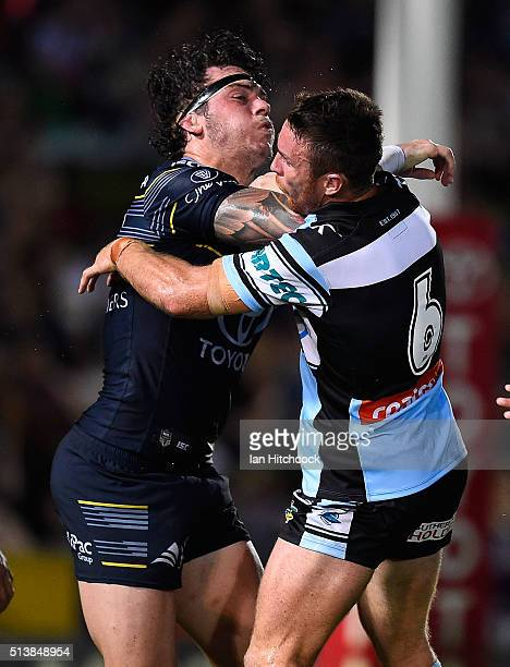 Ethan Lowe of the Cowboys is tackled by James Maloney of the Sharks during the round one NRL match between the North Queensland Cowboys and the...