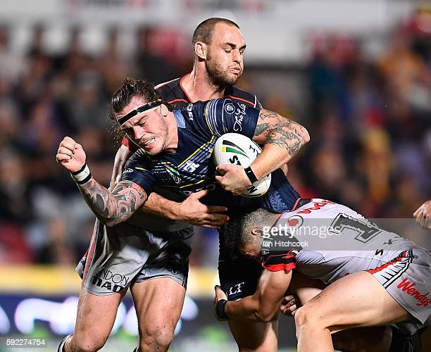 Ethan Lowe of the Cowboys is tackled by Simon Mannering and Nathaniel Roache of the Warriors during the round 24 NRL match between the North...