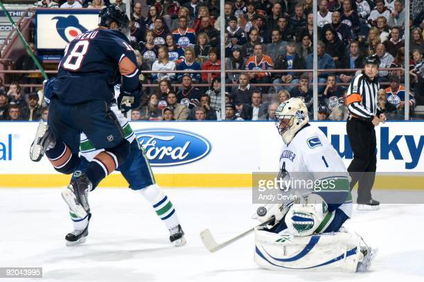 Ethan Moreau of the Edmonton Oilers leaqps out of the way while screening goaltender Roberto Luongo of the Vancouver Canucks who makes the save at...