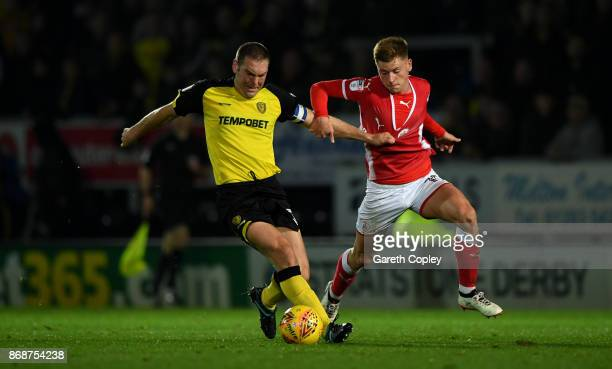 Ethan Pinnock of Barnsley is tackled by Jake Buxton of Burton during the Sky Bet Championship match between Burton Albion and Barnsley at Pirelli...