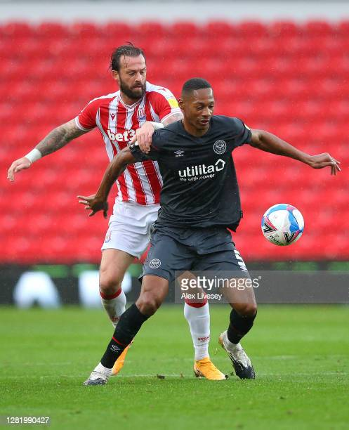 Ethan Pinnock of Brentford is challenged by Steven Fletcher of Stoke City during the Sky Bet Championship match between Stoke City and Brentford at...