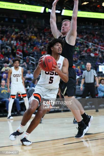 Ethan Thompson of the Oregon State Beavers handles the ball against Alexander Strating of the Colorado Buffaloes during a quarterfinal game of the...