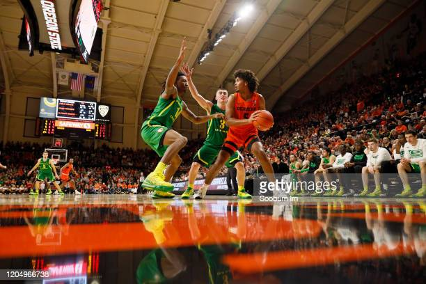 Ethan Thompson of the Oregon State Beavers looks to pass the ball defended by C.J. Walker of the Oregon Ducks and Payton Pritchard during the second...
