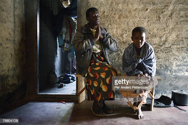 Ethel Dailesi age 44 prays with her daughter Rebecca Masawo age 10 in her livingroom after taking her drugs on August 21 2006 in Mphandula village...
