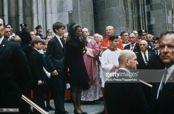 Ethel Kennedy, wearing a black veil, and her children pause on the steps of Saint Patrick's Cathedral, New York following the funeral and requiem...