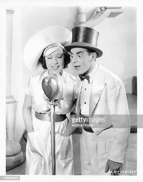 Ethel Merman and Eddie Cantor singing into heart shaped microphone in a scene from the film 'Kid Millions' 1934