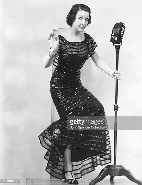 Ethel Merman performs while holding a CBS Microphone.