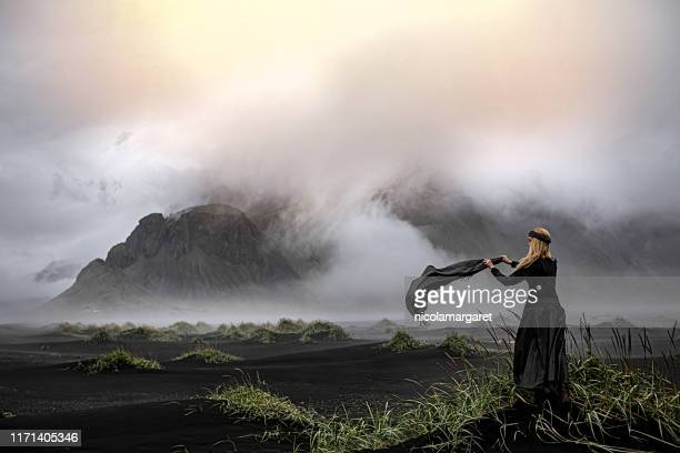 ethereal woman in icelandic landscape - long dress stock pictures, royalty-free photos & images