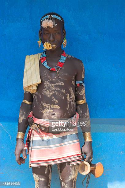 Ethiopia Lower Omo Valley Key Afir Tsemay man in traditional attire with flower in mouth at weekly market