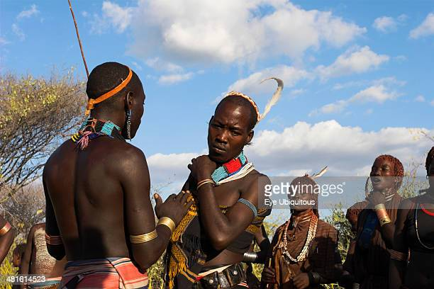 Ethiopia Lower Omo Valley Tumi Hamer Jumping of the Bulls initiation ceremony Hamer men chat whilst women perform ritual dancing around bulls