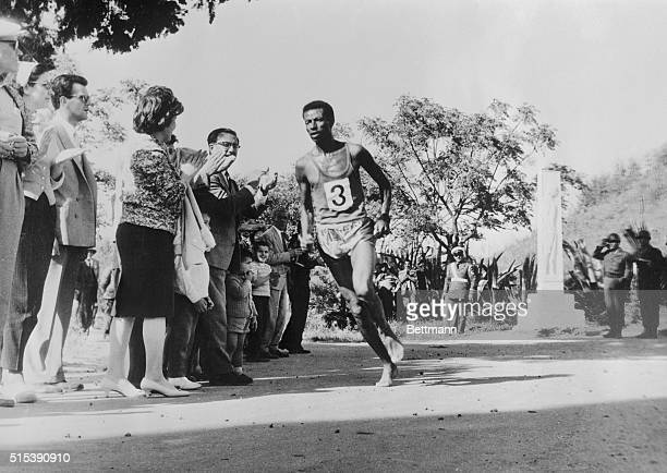 Ethiopian 1960 Olympic champion Bikilla Abebe, running barefooted, dashes past the tomb of the Marathon Warriors, May 7th, on his way to victory in...