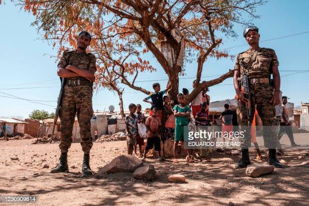 Ethiopian Army soldiers stand as a children stand behind them at Mai Aini Refugee camp, in Ethiopia, on January 30, 2021. - Eritrean refugees in...