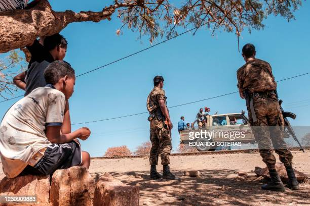 Ethiopian Army soldiers stand as a pick-up truck with militia men passes by at Mai Aini Refugee camp, in Ethiopia, on January 30, 2021. - Eritrean...