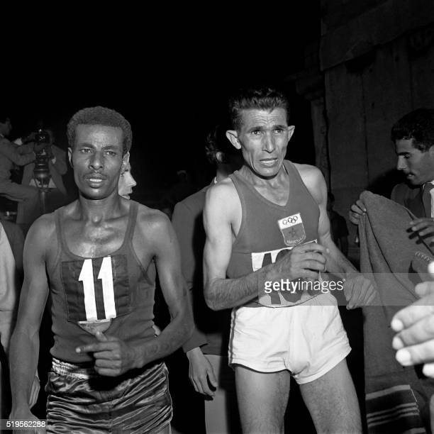 Ethiopian athlete Abebe Bikila nicknamed 'the barefoot runner' and Abdeslam Ghadi regain one's breath after the Olympic marathon event that Bikila...