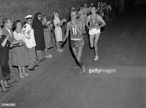 Ethiopian athlete Abebe Bikila runs barefoot for victory in the Rome 1960 Olympic Games marathon after passing Moroccan Abdeslam Radi on September 10...
