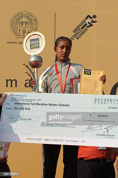 Ethiopian athlete Fita Gadisse poses with her winning cheque and trophy after the Sabarmati Marathon 2011 in Ahmedabad on December 25 2011 Rotich...