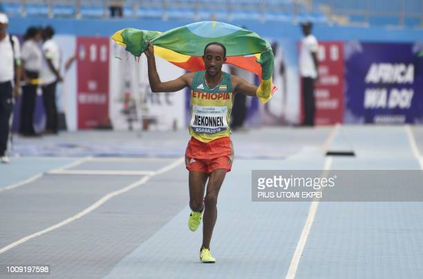 Ethiopian athlete Jemal Mekonnen celebrates winning the first gold medal of the tournament in the 10000 race during the opening of the 21st African...