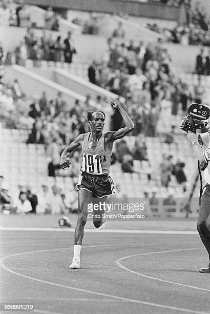Ethiopian athlete Miruts Yifter raises one arm in the air as he leads the field during competition to finish in first place in the final of the Men's...