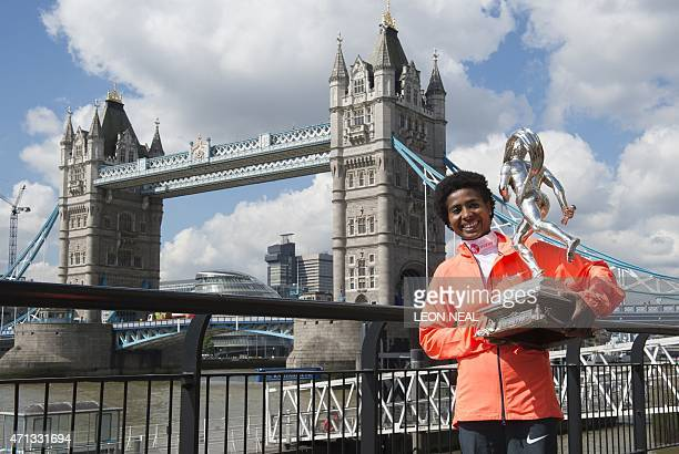 Ethiopian athlete Tigist Tufa poses for pictures with her trophy during a photocall for the winners of the 2015 London Marathon in central London on...