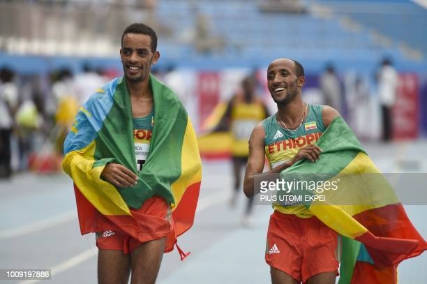 Ethiopian athletes Berta Andamlak and Jemal Mekonnen celebrate winning the first gold and silver medals of the tournament in the 10000 race during...