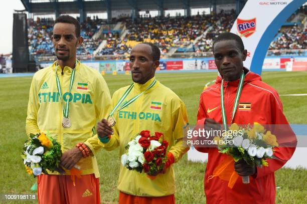 Ethiopian athletes Berta Andamlak Jemal Mekonnen and Ugandian athlete Timothy Toroitich celebrate their medals in the tournament in the 10000 race...